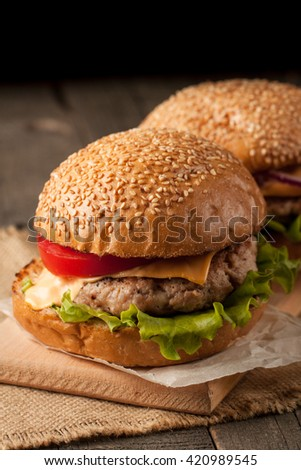 Close-up photo of home made hamburger with beef, onion, tomato, lettuce, cheese and spices. Fresh burger closeup on wooden rustic table with potato fries and chips. - stock photo