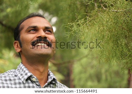 Close-up photo of hopeful, relaxed & happy asian/indian man looking confidently ahead. The executive is wearing a formal shirt & the picture is shot in natural settings - stock photo
