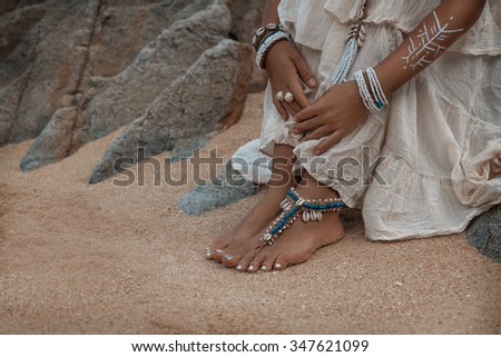 close up photo of legs with boho anklets - stock photo