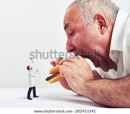 close up photo of man eating burger and small doctor looking at him and protesting against junk food - stock photo