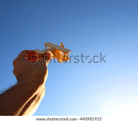 Close up photo of man's hand holding wooden toy airplane against the sky