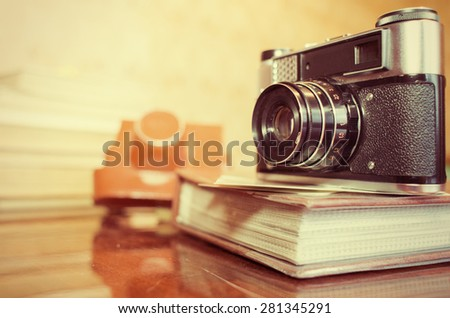 close up photo of old camera lens over wooden table - stock photo