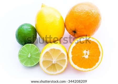 Close up photo of one cut-in-half slice of lime, lemon, an orange, with one  whole lime, lemon, an orange behind. The background is isolated. - stock photo