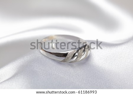 Close up photo of platinum or silver ring on white textile - stock photo