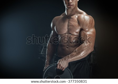 Close up photo of power athletic man doing exercises with barbell plate. Muscular body on dark background.  - stock photo