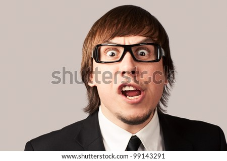 Close-up photo of screaming businessman, on a gray background - stock photo