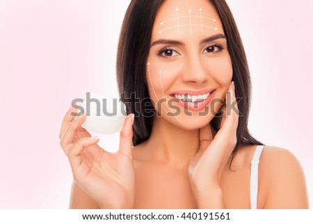 Close-up photo of sensetive pretty woman holding jar of cream and touching her face with arrows of effect - stock photo