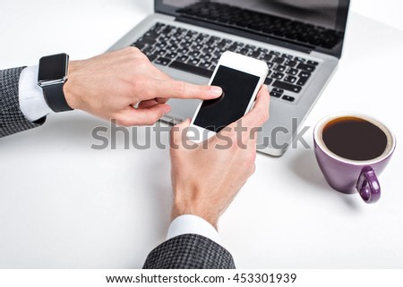 Close up photo of stylish handsome young man isolated on white background. Man with smart watch using laptop and mobile phone - stock photo