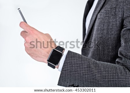 Close up photo of stylish handsome young man isolated on white background. Man with smart watch using mobile phone - stock photo