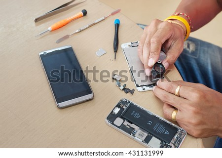Close-up Photo Of Technician Hand Repairing Cellphone - stock photo