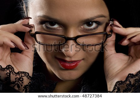 Close-up photo of the beautiful secretary face which is looking mysteriously from the glasses - stock photo