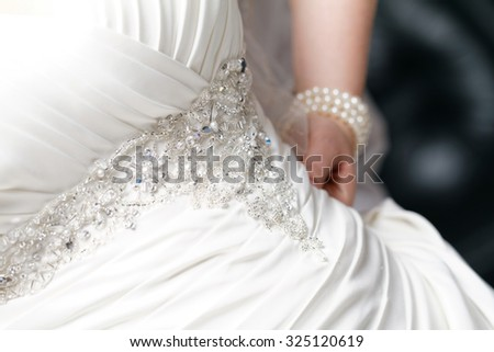 Close up photo of the bride hand in her dress - stock photo