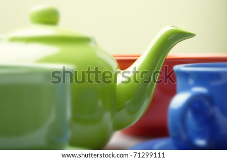 Close-up photo of the fragment of tea service consisting of teapot and cups. Natural color. Shallow depth of field added by the lens for natural view - stock photo