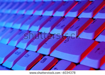Close-up photo of the keyboard of an open notebook; blue red tone - stock photo