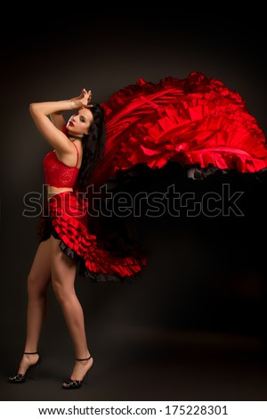 Close-up photo of the lady in gypsy costume dancing flamenco  on a gray background - stock photo
