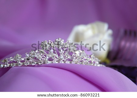 Close-up photo of the silver or platinum (white gold) diadem with diamonds on a lilac background. In the background are visible jewelry rose. Tiara for the bride. - stock photo