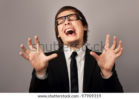 Close-up photo of upset crying businessman, on a gray background - stock photo