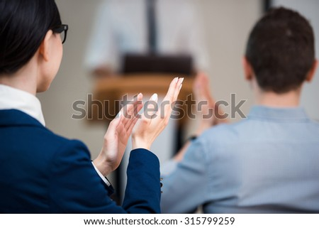 Close up photo of woman hands clapping while businessman making presentation with whiteboard on seminar or meeting to business people