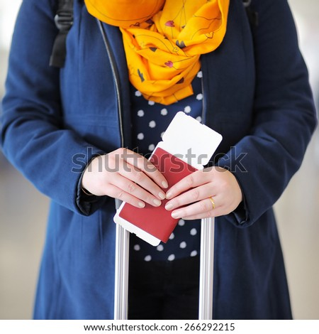 Close up photo of woman holding passport and boarding pass at the airport  - stock photo