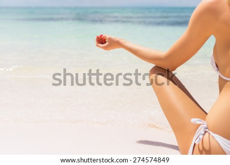 Close-up photo of woman meditating on the beach - stock photo