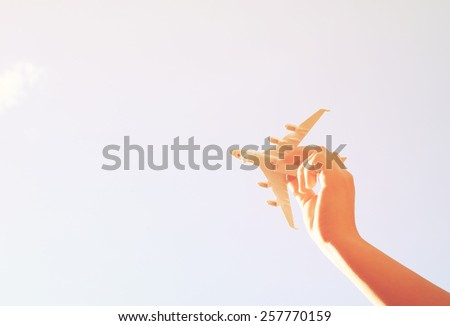 close up photo of woman's hand holding toy airplane against  sky. image is retro filtered - stock photo