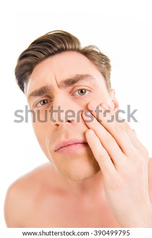 Close up photo of young attractive man expertising his skin