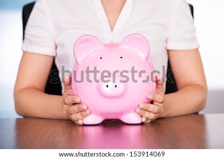 Close-up Photo Of Young Businesswoman Holding Piggybank - stock photo