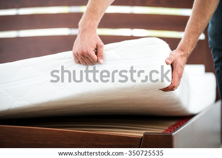 Close up photo of young man demonstrating quality of mattress - stock photo