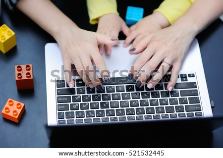 Close up photo of young mother working oh laptop with her toddler child