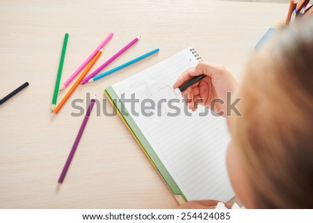 Close up photo of young school girl with pencils writing while sitting in school desk - stock photo
