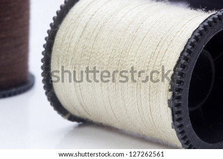 Close-up photograph of a beige spool of thread. - stock photo