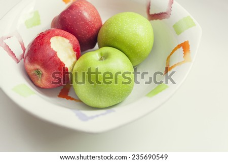 Close up photograph of a bitten apple in a group of apples in bowl - stock photo