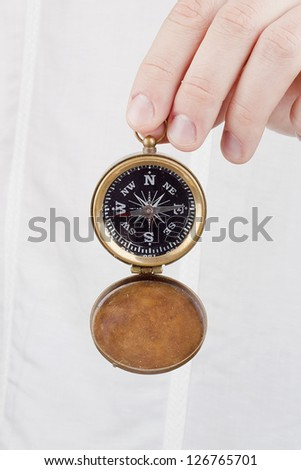 Close-up photograph of a hand holding an old compass. - stock photo
