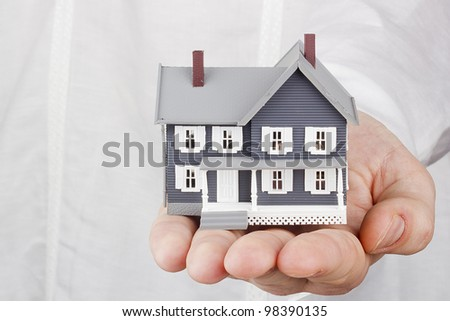 Close-up photograph of a miniature house in a man's hand. - stock photo