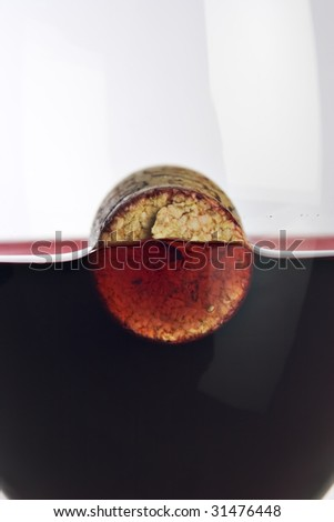 Close up photograph of a wine bottle cork floating in a glass of wine - stock photo