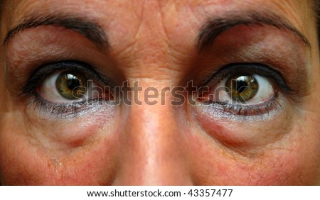 Close up photograph of in an insomniac's eyes with eyeliner on. - stock photo
