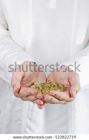Close-up photograph of man's hands holding golden coins. - stock photo