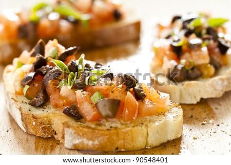 Close up photograph of three tomato and olives bruschetta - stock photo