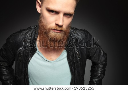 close up picture of a casual young man with a long beard looking into the camera. on a dark studio background