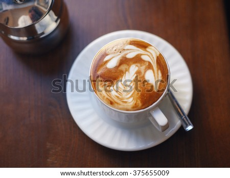 Close up picture of a cup of coffee with a picture on it. - stock photo