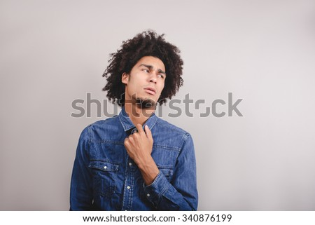 Close up picture of a handsome man pulling his shirt - stock photo