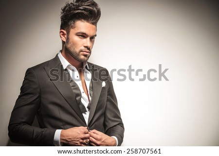 Close up picture of a handsome young business man unbuttoning his jacket while looking away from the camera. - stock photo