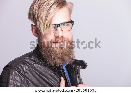 Close up picture of a young blond casual man smiling to the camera while pulling his collar. - stock photo
