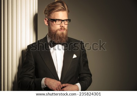 Close up picture of a young elegant business man looking away from the camera while closing his jacket. - stock photo