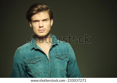 Close up picture of a young fashion man looking away from the camera, thinking. - stock photo