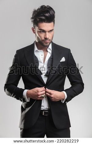 Close up picture of an elegant young man in tuxedo closing his jacket, looking away from the camera. On grey background. - stock photo