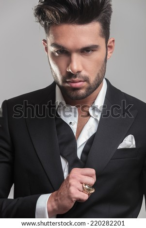 Close up picture of an elegant young man looking at the camera while ajusting his tuxedo. On grey background - stock photo