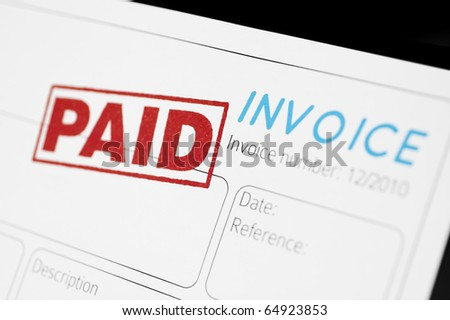 Close-up picture of an invoice with red paid stamp. - stock photo