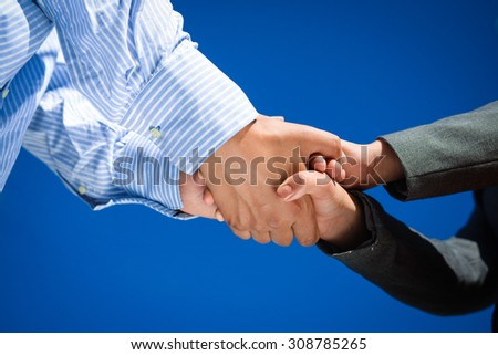 close up picture of business people handshaking with both hands on blue sky sunny outdoors background - stock photo