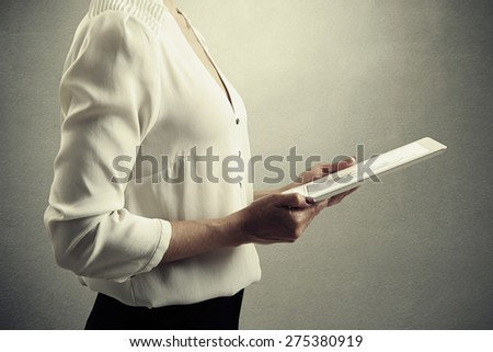 close up picture of businesswoman holding tablet pc with bar graphic over grey background  - stock photo